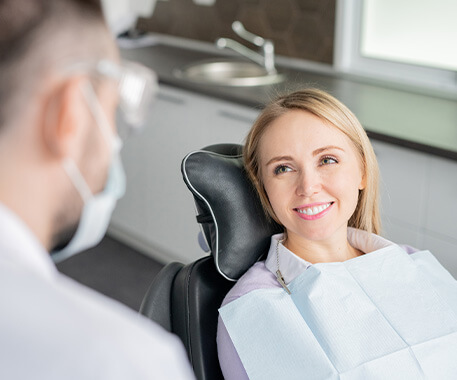 dentist speaking with woman sitting in a dental chair