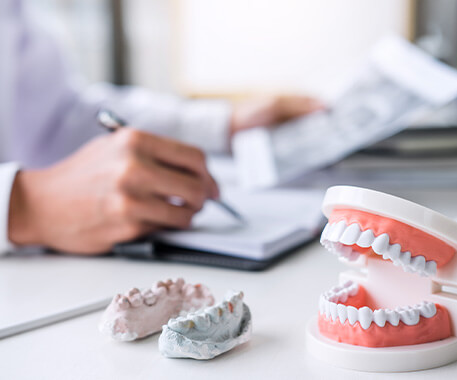 closeup of models of teeth sitting on a dentist's desk while he writes notes in the background